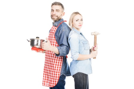 Attractive woman with hammer and her husband with saucepan looking at camera on white background