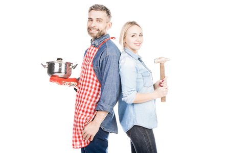 Caucasian man with saucepan and attractive woman with hammer smiling happily on white background