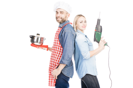 Portrait of male chef with saucepan and pretty woman with hand drill smiling at camera on white background