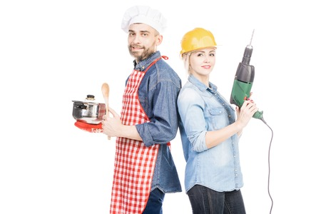 Portrait of male cook with saucepan and pretty woman in helmet with drill smiling at camera on white background