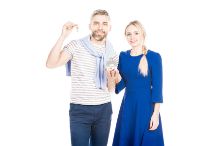 Happy couple holding home keys against white background