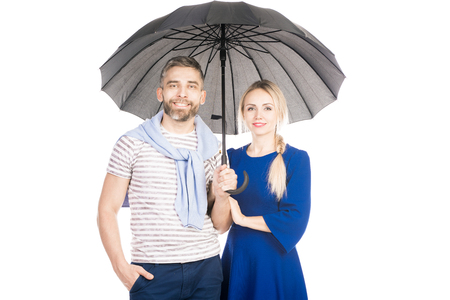 Portrait of young couple with umbrella isolated on white background Фото со стока