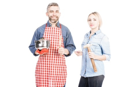 Portrait of smiling bearded man with saucepan and attractive woman with hammer standing on white background Фото со стока