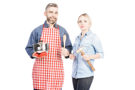 Bearded Caucasian man with saucepan and his wife with hammer smiling at camera on white background