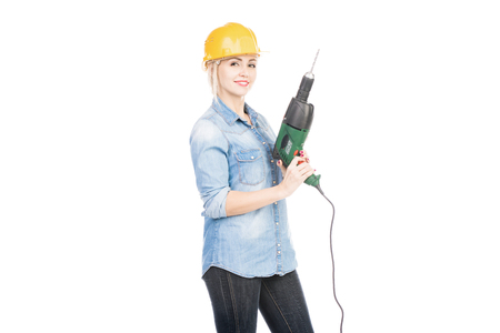 Portrait of attractive female constructor in helmet with hand drill smiling at camera on white background