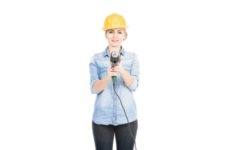 Portrait of Caucasian woman holding hand electric drill like pistol and smiling at camera on white background