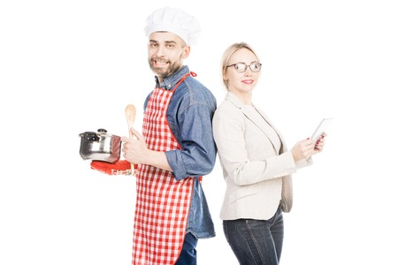 Portrait of cheerful male cook and confident businesswoman smiling at camera on white background