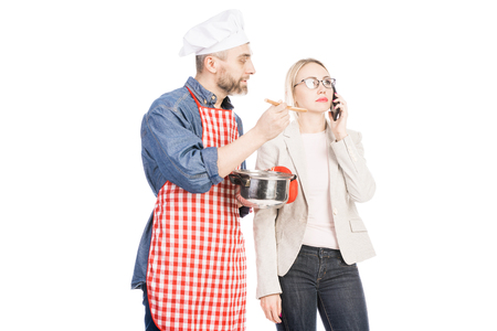 Male chef holding saucepan and feeding attractive woman talking on smartphone on white background