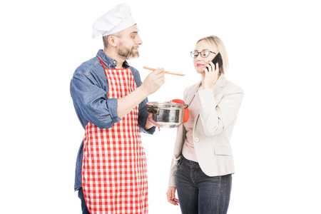 Caucasian male cook holding saucepan and feeding beautiful woman talking on smartphone on white background