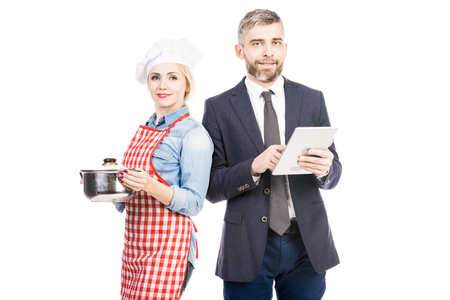 Portrait of successful businessman with tablet and attractive female chef looking at camera  on white background