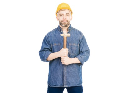 Portrait of bearded Caucasian man in helmet holding hammer and looking at camera on white background