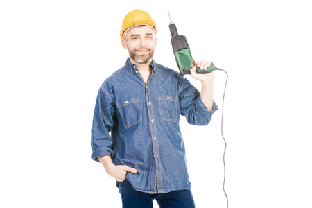 Portrait of bearded Caucasian man in helmet holding electric drill and smiling at camera on white background