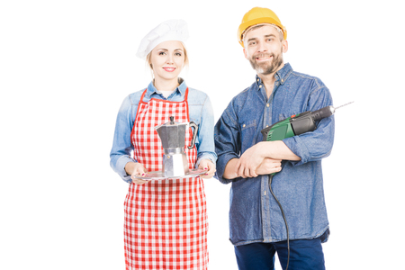 Attractive female cook with coffee pot and bearded man with electric drill smiling at camera on white background Фото со стока