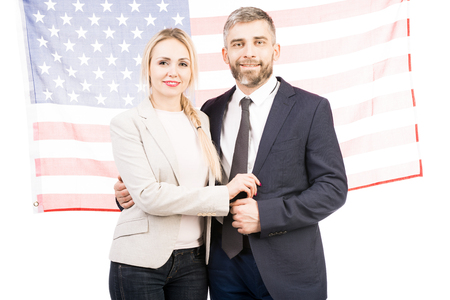Portrait of attractive Caucasian couple standing against american flag and smiling at camera cheerfully