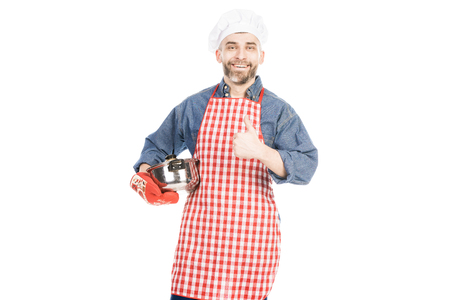 Caucasian man in apron with saucepan showing thumb up and smiling at camera on white background