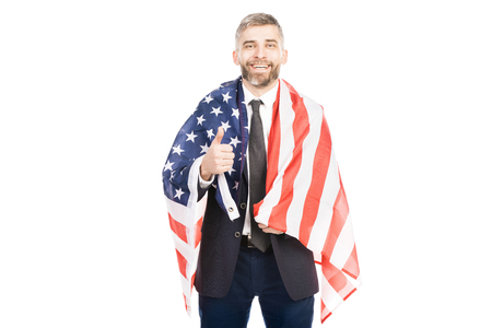 Portrait of handsome bearded man holding US flag, showing thumb up and smiling at camera on white background