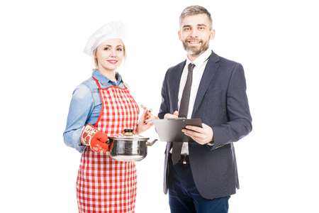 Portrait of attractive female chef and confident male manager smiling at camera against white background Фото со стока