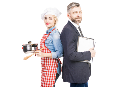 Portrait of beautiful female cook and successful businessman standing on white background and smiling at camera Фото со стока