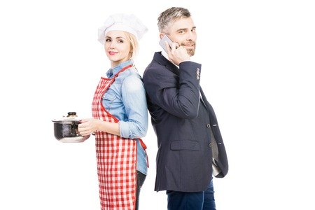 Portrait of happy female cook with saucepan and confident businessman talking on smartphone on white background
