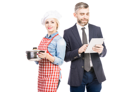 Portrait of attractive female cook smiling at camera and confident male manager using tablet on white background
