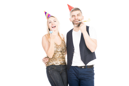 Portrait of young Caucasian couple blowing party horns and laughing happily while standing on white background