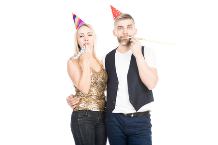 Portrait of beautiful Caucasian couple with party hats blowing party horns and looking at camera on white background