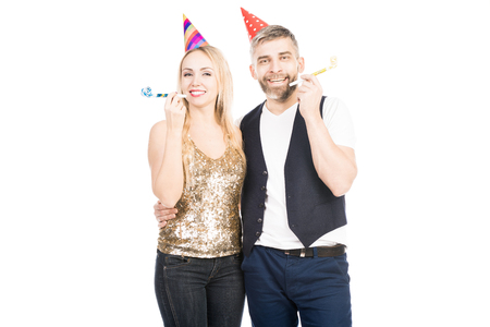 Portrait of attractive Caucasian couple with party hats and horns smiling at camera cheerfully on white background