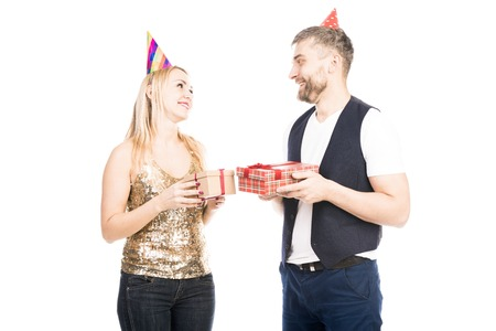 Portrait of happy Caucasian man and woman in party hats giving each other presents on white background