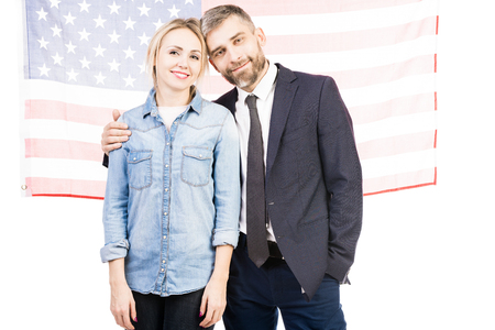 Portrait of handsome bearded man embracing pretty woman and smiling happily on american flag background