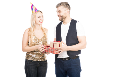 Portrait of beautiful woman receiving wrapped presents from bearded man and smiling joyfully on white background