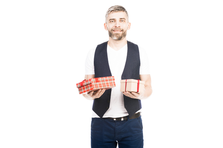 Portrait of attractive bearded Caucasian man holding wrapped gifts and smiling at camera isolated on white background