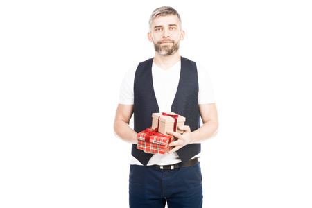 Portrait of handsome middle-aged man holding wrapped birthday presents and looking at camera  on white background Фото со стока