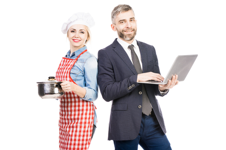 Portrait of beautiful female chef and confident male entrepreneur with laptop smiling at camera on white background