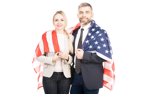 Portrait of beautiful couple smiling at camera while standing on white background with US flag on their backs