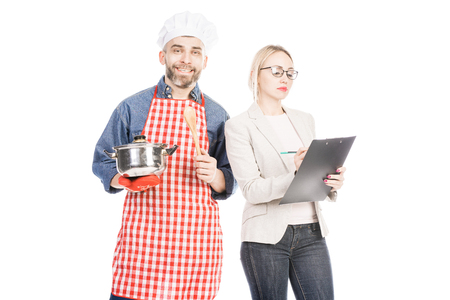 Portrait of happy male chef and attractive woman with clipboard standing isolated on white background