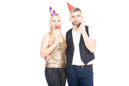 Portrait of happy Caucasian man and woman blowing party horns and smiling at camera on white background