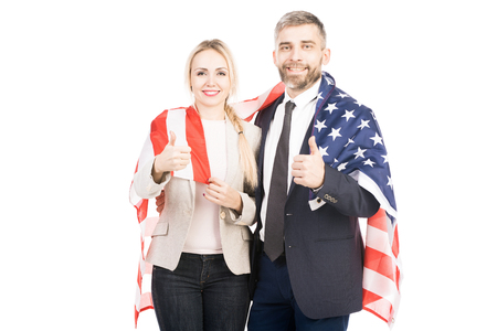 Portrait of happy Caucasian couple with US flag showing thumbs up and smiling at camera on white background