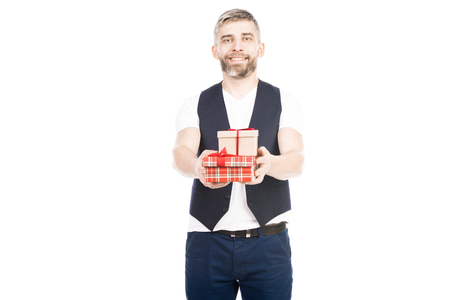 Portrait of smiling man standing with gift boxes on white background