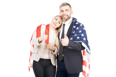 Portrait of happy Caucasian couple with american flag showing thumbs up and looking at camera on white background