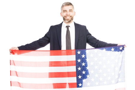 Portrait of middle-aged bearded man in suit holding US flag and smiling at camera cheerfully on white background