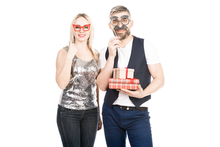 Portrait of smiling couple in mask holding presents
