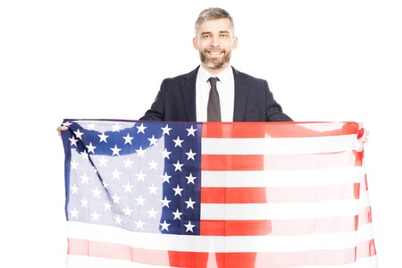 Portrait of handsome bearded man in suit holding american flag and smiling at camera happily on white background Фото со стока