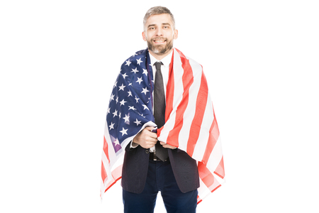 Portrait of middle-aged bearded Caucasian man holding american flag and smiling at camera on white background