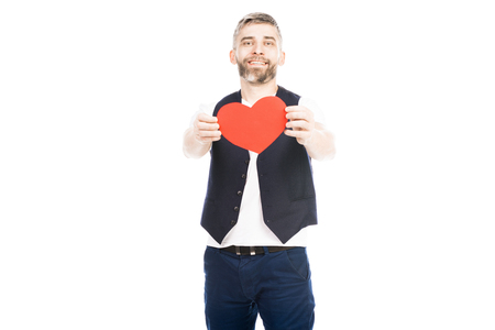 Portrait of happy young man standing with big valentines on white background