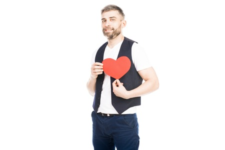 Portrait of man holding red heart. He is celebrating Valentines Day Фото со стока