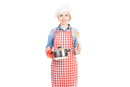 Portrait of young pretty woman in chef toque holding saucepan and smiling at camera on white background