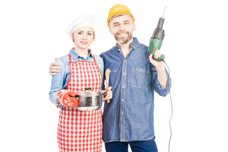 Portrait of beautiful woman in chef hat and bearded man with drill smiling at camera on white background
