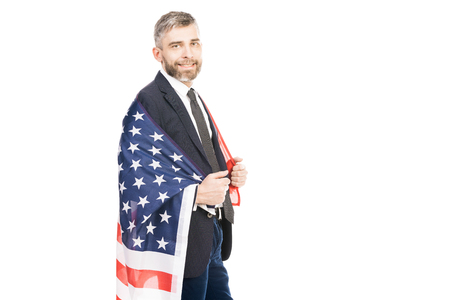 Portrait of confident middle-aged man in suit holding US flag and smiling at camera on white background