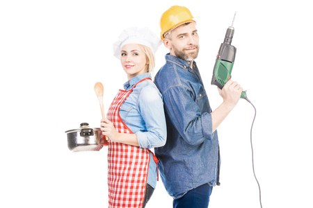 Portrait of pretty woman in chef toque and bearded man with electric drill posing on camera against white background