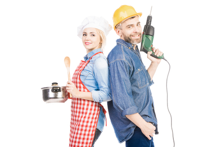 Attractive female cook with saucepan and bearded man with hand drill smiling at camera on white background